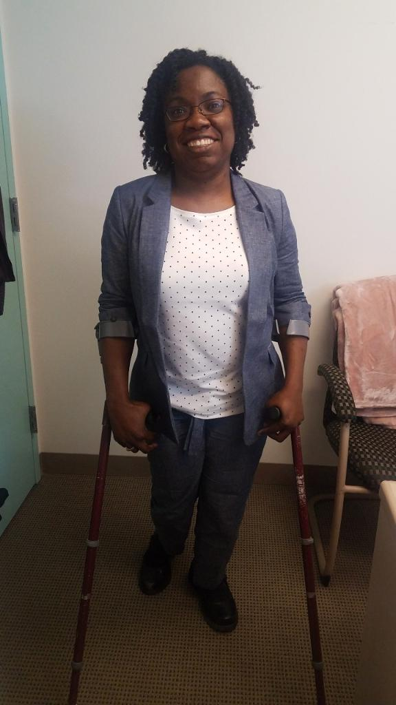 Black woman with curly natural, black hair and glasses in a blue chambray suit and white and blue polka dot top standing on crutches in an office.