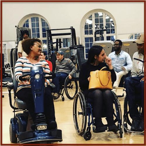 fyra personer i rullstol på ett gym och spelar bocci