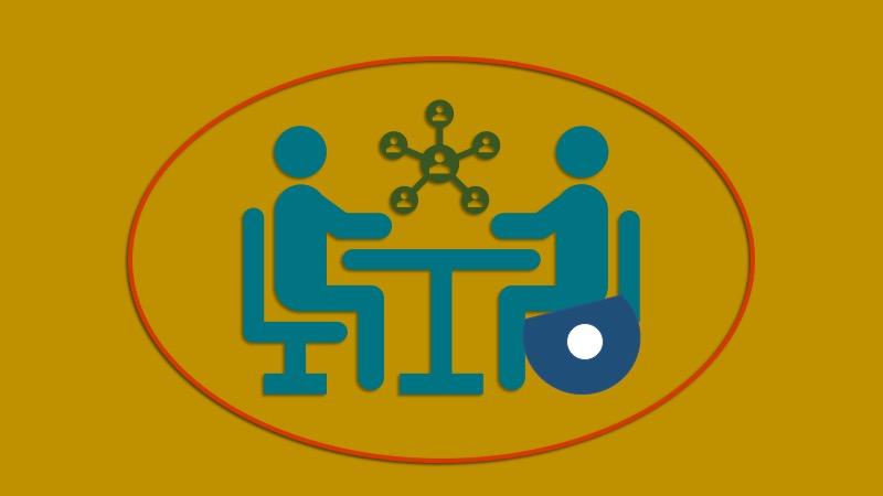 Två figurer som föreställer personer som samtalar kring ett runt bord