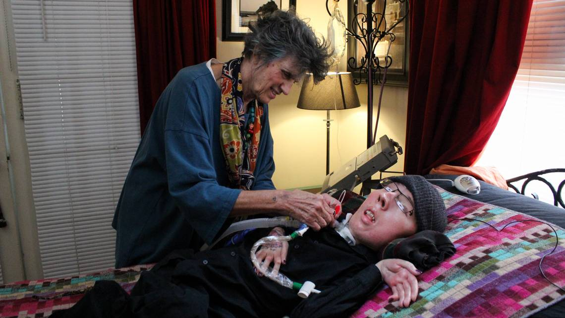 Karen Clay operates a medical ventilator to help her son Michael Phillips, 36, breathe. Michael has spinal muscular atrophy and is confined to his bed. He can breathe only with the aid of a machine. Here, they are photographed at their Tampa home July 19, 2017. ALESSANDRA DA PRA Tampa Bay Times