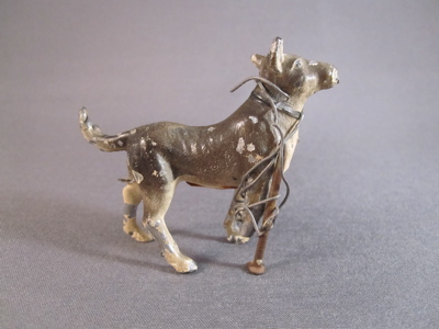 Cold painted cast lead dog figure, c.1930. A small nail and short length of wire replaces a tiny toy dog's missing leg.