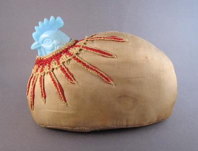 "Milk glass hen pin cushion, c.1890. This  ""make-do"" pin cushion is made from a broken lid. ""I assume the intact bottom half was reused as a dish, but the top half remains were encased in fabric and cotton batting, crocheted with red ""feathers"" around the neck and transformed in to a practical pin cushion."""