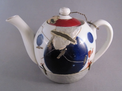 """Eastern European teapot, c.1925. """"No part of this poor teapot has escaped damage, making it by far the most altered piece in my collection. There are 18 metal support staples, a replaced hand-hammered tin base, a large tin patch on one side, a mended chip on the lid grafted from another lid entirely, and a wire tether holding the lid in place. The  numerous metal staples (aka rivets) appear to be machine made and are reinforced with cement."""""""