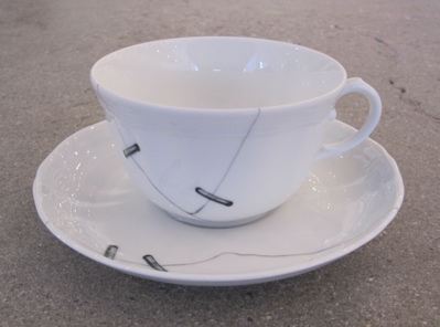 "This is actually a faux repaired tea cup. These were created in 2010 by architect and product designer Paola Navone and feature printed cracks ""repaired"" with trompe l'oeil metal staples."