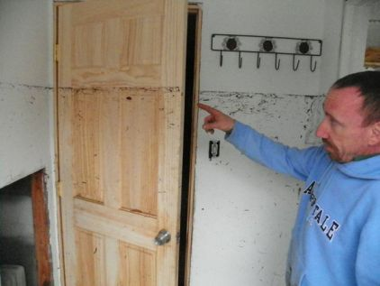 "Original caption: ""Port Monmouth resident Jules Johnson points out how high flood waters from Hurricane Sandy got inside his home."" Rob Spahr / NJ.com"