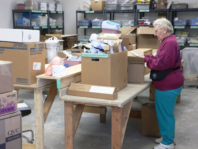 Figure 1. An IHM volunteer whom I call Harriet, and with whom I regularly worked, sorting medical donations; at the time of my fieldwork in 2005-2006, Harriet, a retired missionary nurse, had spent 16 years volunteering at the agency. She passed away in 2010.