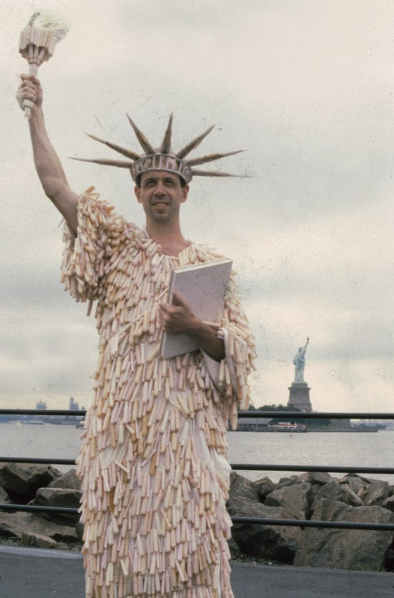 person in a statue of liberty costume made of tampon applicators posing in New York City, with the statue of liberty visible behind them