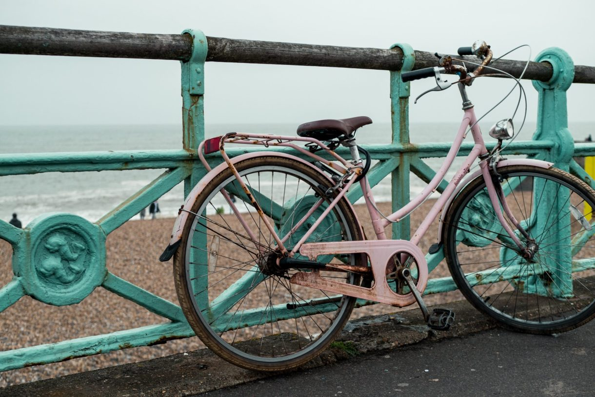 A hire bike leans against a turquoise fence. The beach is in the background