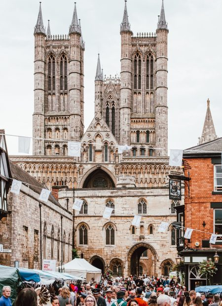 Lincoln cathedral dominates the photo, white flags are strung across the castle square and crowds flood a christmas market in the front