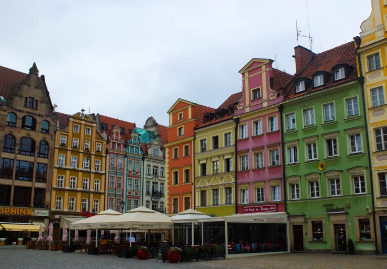 Colourful Polish Houses in yellow, pink and teal line a cobbled street. There are marquees outside restaurants.