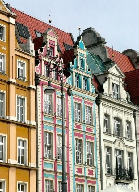 Colourful Polish Houses in yellow, pink and teal line a cobbled street.