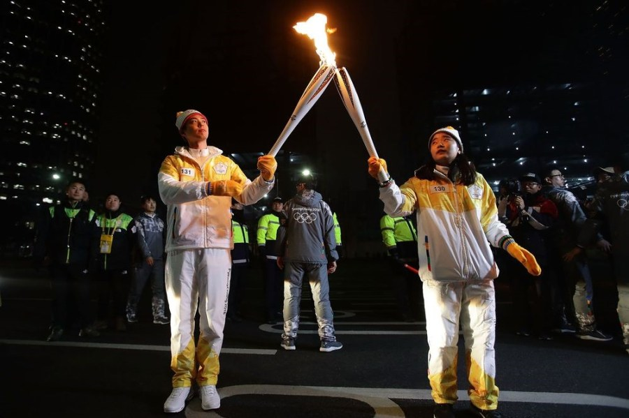 South Korean actor Park Bo-Gum, left, holds the PyeongChang 2018 Winter Olympics torch during the torch relay in Seoul on Jan. 16, 2018.Photographer: Chung Sung-Jun/Getty Images AsiaPac