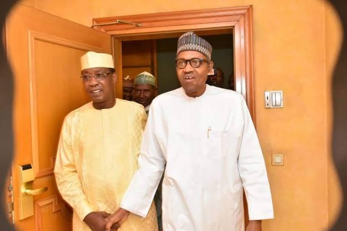 Nigeria's President, Muhammadu Buhari holding hands with Chad President, Idris Derby (R)