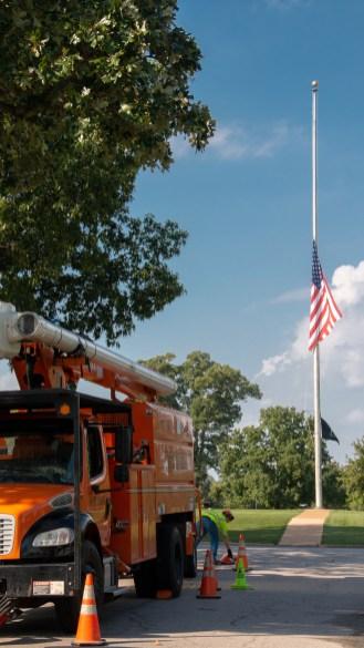 A truck from Asplundh set up under an oak tree near the entrance to Jefferson Barracks National Cemetery.