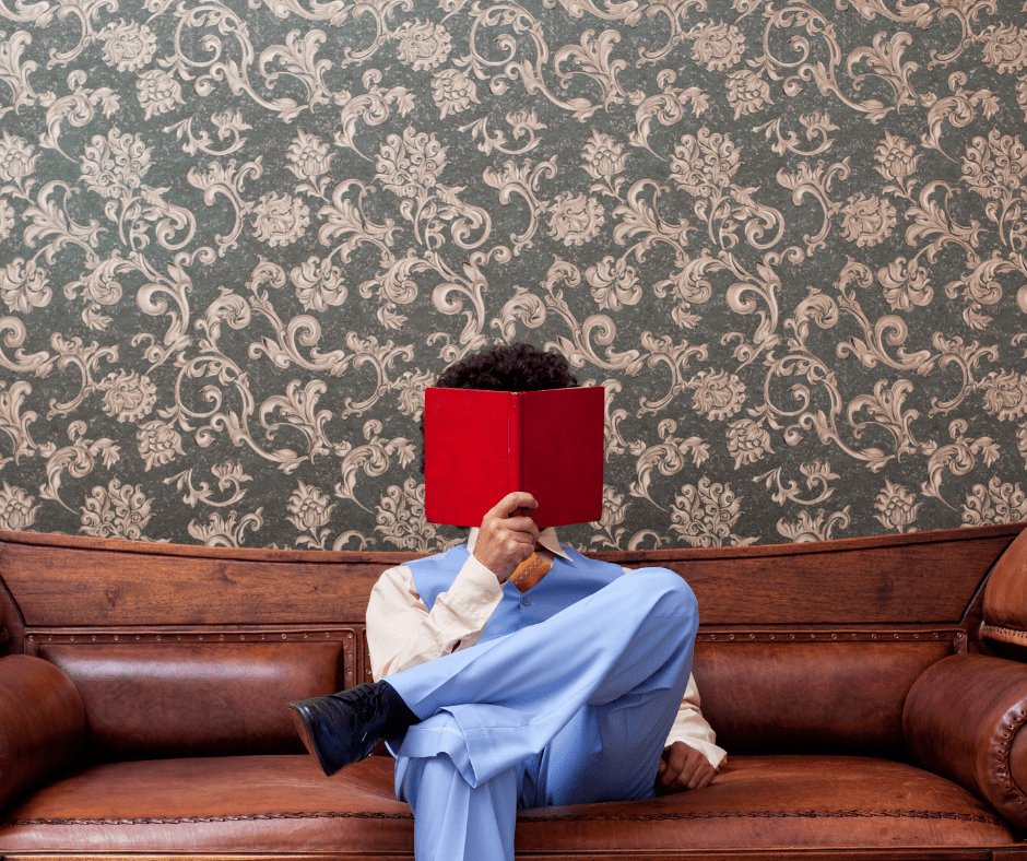 Man wearing a blue leisure suit reading a book