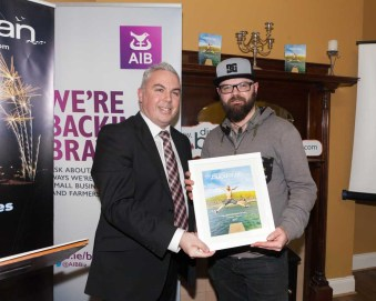 Shane presents photographer Peter Mayne with a framed copy of the brochure cover