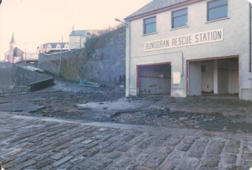 The lifeboat station's doors are washed away and the boat is carried from the pier and dumped onto the Main Beach, damaging it beyond repair.