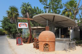 a beach side stand with brick oven made pizza and bread
