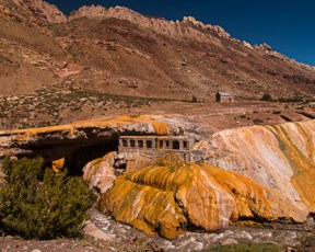 This is the Puente del Inca in the Andes mountains, a natural bridge crossing the Las Cuevas river at about 8,000 ft above sea level. The building used to be a hotel and the rocks are colored by iron thermal -mineral sediments