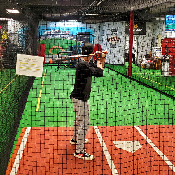 Child enjoying the batting cage at Evolution Sports Excellence in Leduc, AB