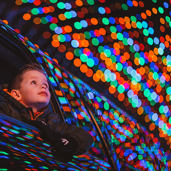 Boy gazing out of the window of a vehicle at Christmas lights