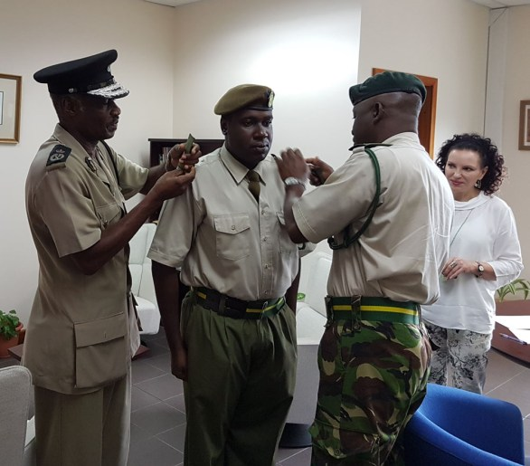 Lt Glenroy Foster receives his new pips from his father Commissioner of Police Steve Foster and RMDF Commander Alvin Ryan as HE Governor Carriere looks on.