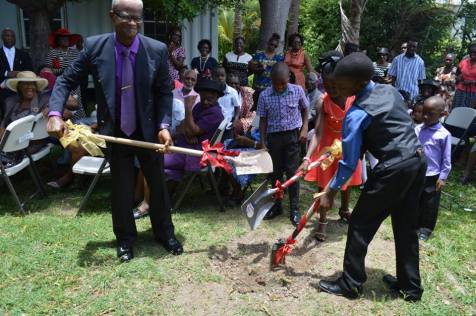 Retired pastor Bishop Abraham Riley breaks ground with two of the church's youngest members Kimani Phill and Rashid Watts.
