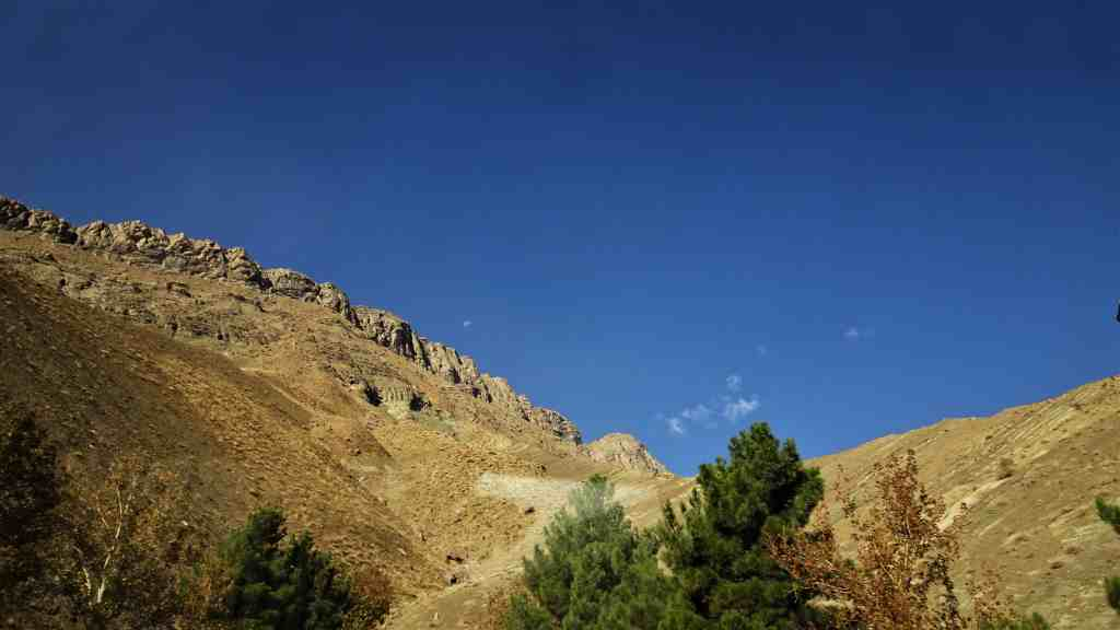 Chalus Road, dry mountains, green trees and a translucent moon in the distance