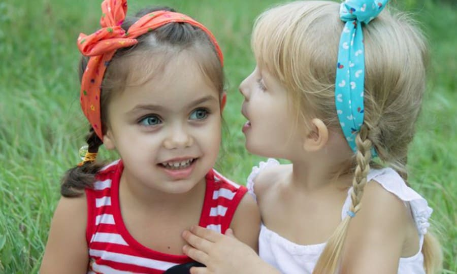 why are social skills important- two young friends sharing a secret