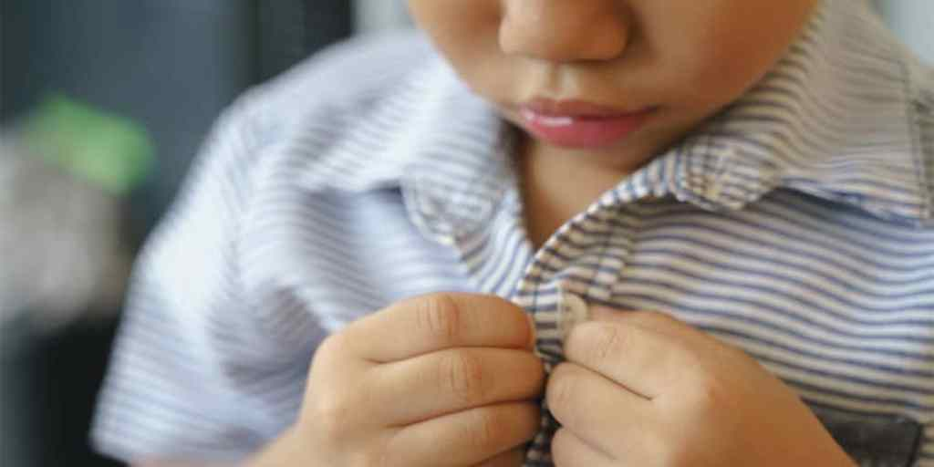 fine motor activities for toddlers-young toddler boy buttoning his own shirt