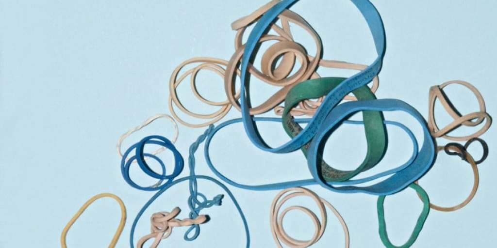 fine motor activities for preschoolers-rubber band fine motor activities-pile of blue, green and tan rubber bands in a variety of sizes