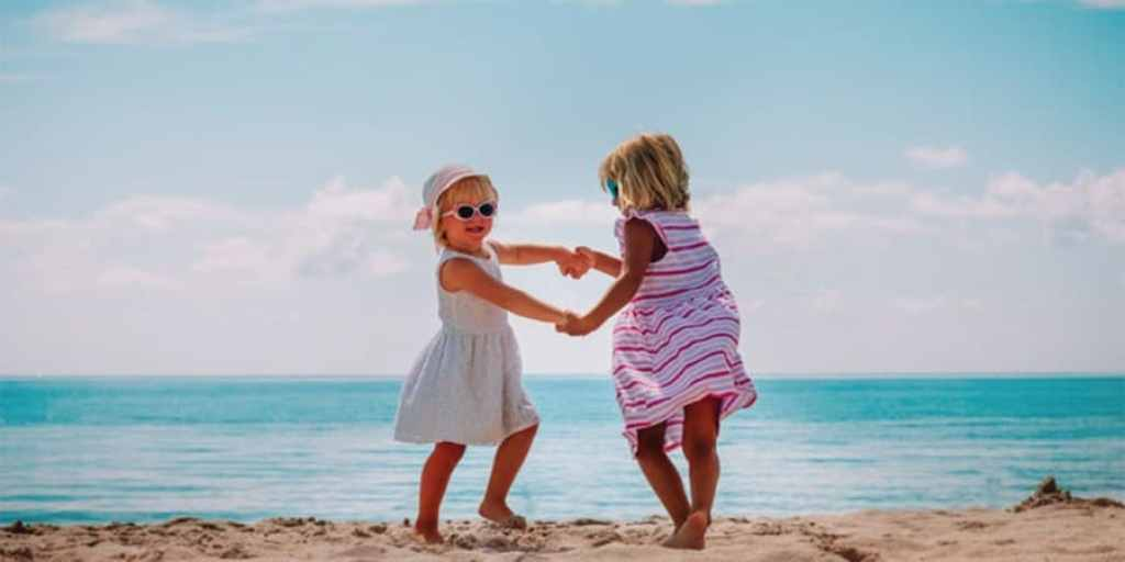 gross motor games-two young girls playing ring around the rosie on the beach
