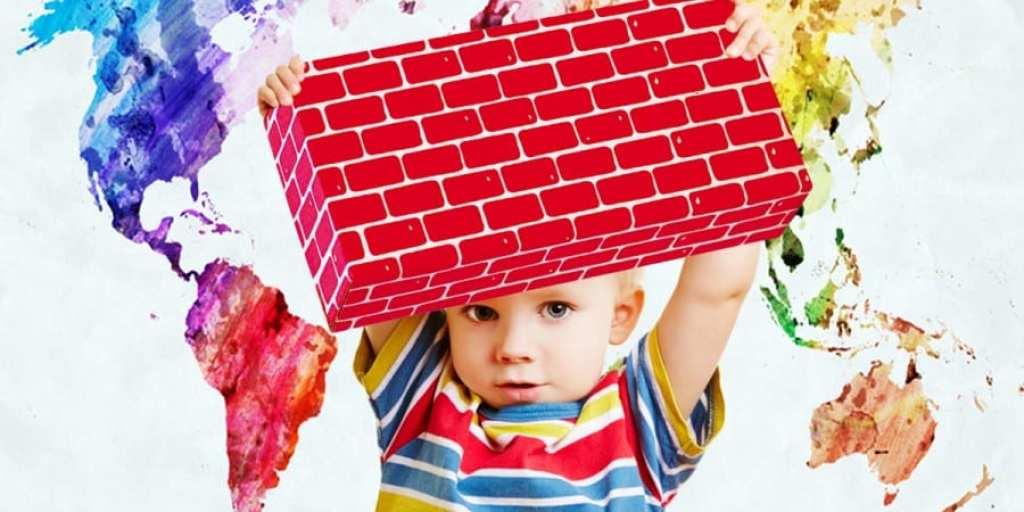 gross motor activities-giant blocks-toddler boy holding up a red brick jumbo block confidently