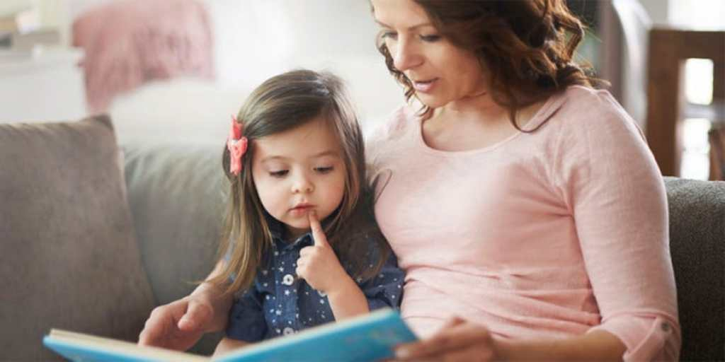 language development- mother and young daughter reading a book together