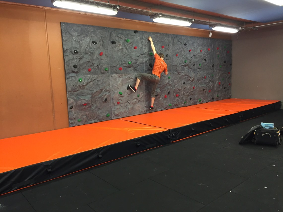 A climber is bouldering across the traverse wall