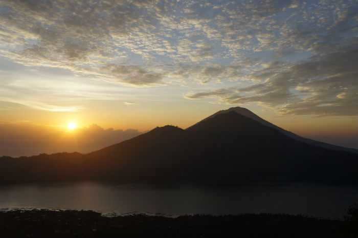 View from the top of Mount Batur at sunrise. You get a great view over the lake with the hills rising in the background.