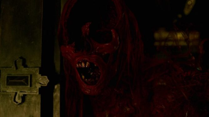 One of the Crimson Peak red ghosts opens its ghastly mouth with its upper face missing.