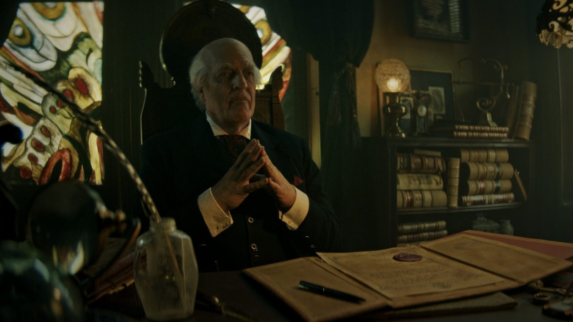 Clancy Brown as Montgomery Dark sits and ponders at his desk in Ryan Spindell's 'The Mortuary Collection'