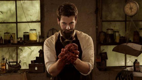 Director and writer Ryan Spindell poses in costume as a butcher holding a bloody heart in his hands.