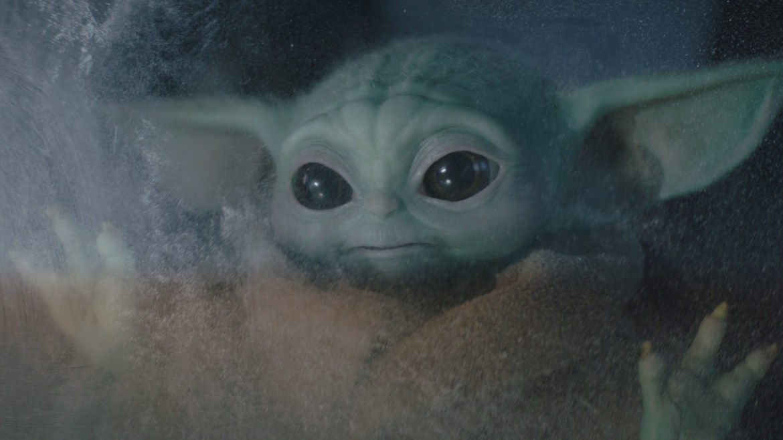 Baby Yoda looking outside of a frozen window as seen in Chapter 10 of The Mandalorian.