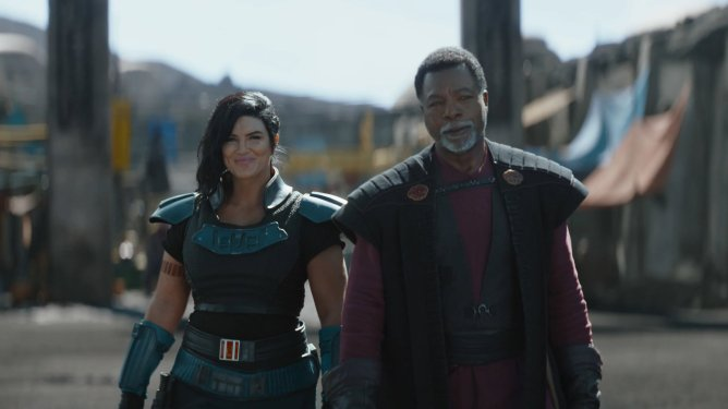 Gina Carano as Cara Dune and Carl Weathers as Greef Karga stand together in joy as seen in Chapter 12 of The Mandalorian.
