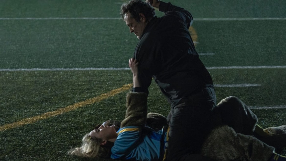 Vince Vaughn tackles Kathryn Newton in an empty football field as he raises his hand to stab her in the chest as seen in Freaky.