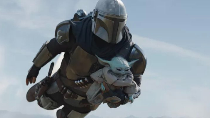 Pedro Pascal's Mando carries Baby Yoda as he flies through the sky with his jet-pack as seen in Chapter 14 of The Mandalorian.