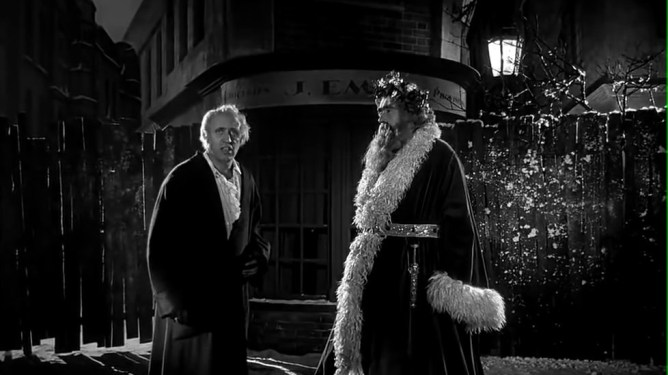 Ebeneezer Scooge being visited by the Ghost of Christmas present in the 1951 film adaptation titled Scrooge.