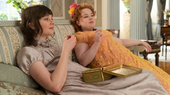 Claudia Jessie and Nicola Coughlan relax while sharing snacks on a couch as seen in Bridgerton on Netflix.
