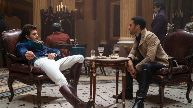 Jonathan Bailey and Regé-Jean Page sharing drinks in a hall as a pianist serenades them as seen in Bridgerton on Netflix.