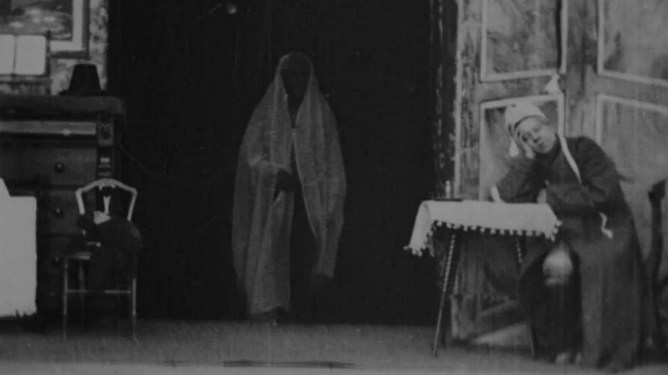 The Ghost of Christmas Future visiting Ebeneezer Scrooge in the first black and white and silent film adaption from 1901 titled Scrooge, or Marley's Ghost.