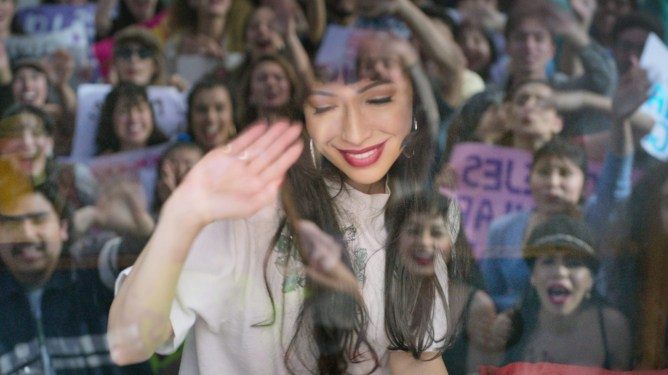 Christian Serratos as Selena waving at a crowd of emotional fans as seen in 'Selena: The Series' on Netflix.