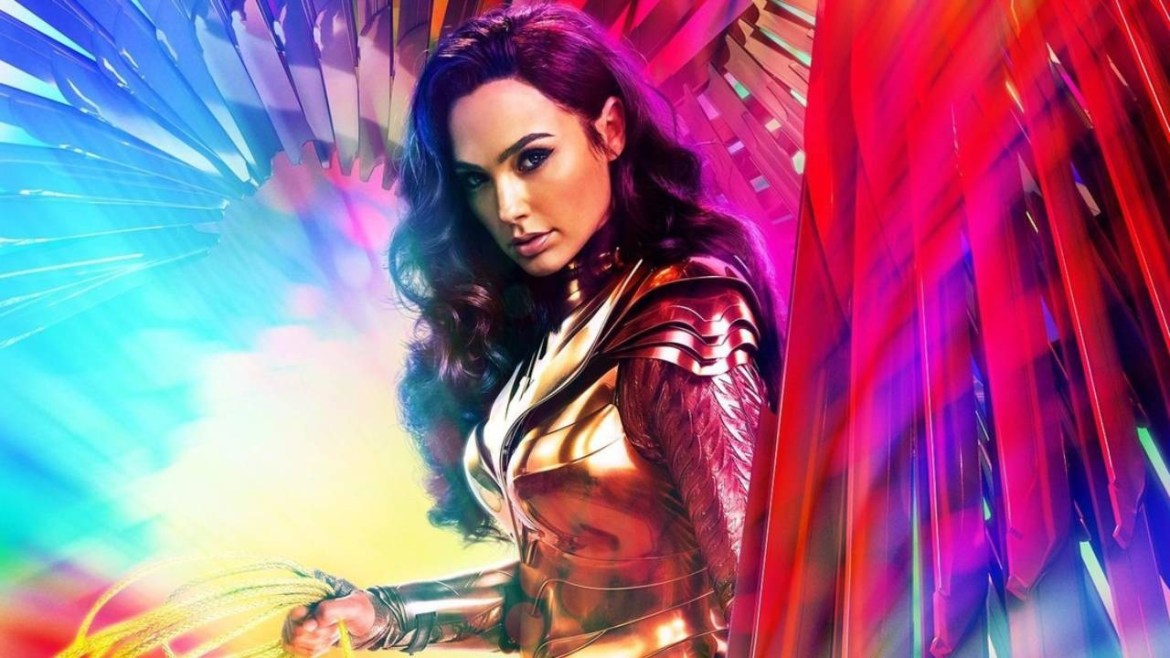 Gal Gadot looking stunning in golden armor around colorful promotion for Wonder Woman 1984.
