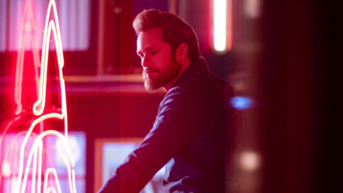 Alexander Skarsgård as Randall Flagg standing by red neon lights as seen in The Stand on CBS All Access.